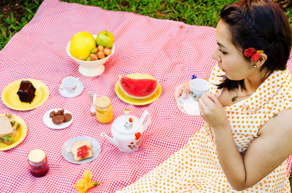 Woman in a yellow dress having a picnic on a pink blanket