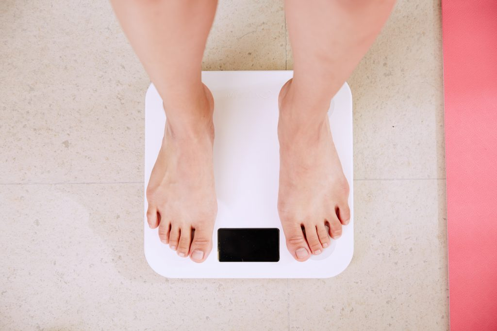 Person standing on a white scale/ diet culture